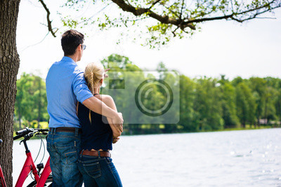 Bild Rear view of lovely young couple looking at lake