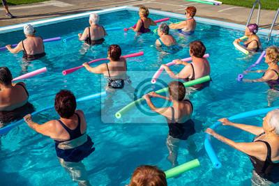 Bild Rear view of senior aqua gym class with foam noodles.