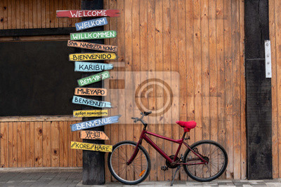 Bild Red Bike Next to a Post with Welcome Signs in Several Different Languages.  English, Afrikaans, German, Xhosa, Spanish, Swahili, Portuguese, Oshiwambo, Italian, Russian, French, Japanese, Korean