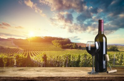 Bild Red wine bottle and wine glass on wodden barrel. Beautiful Tuscany background