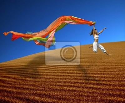 Regenbogen Frau springt über die Dünen
