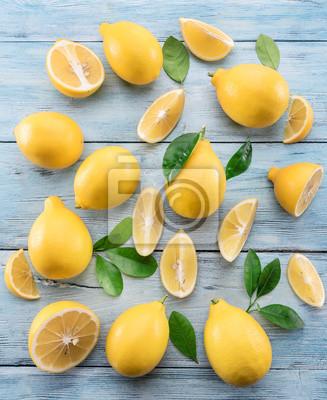 Bild Reife Zitronen und Zitronenblätter auf blauem hölzernem Hintergrund. Draufsicht.