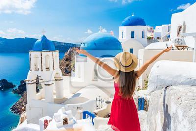Bild Reise-glückliche Frau Europa-Reise. Mädchentourist, der Spaß mit den offenen Armen in der Freiheit in Santorini-Kreuzfahrtfeiertag, Sommer europäischer Bestimmungsort hat. Rote Kleider- und Hutperson.