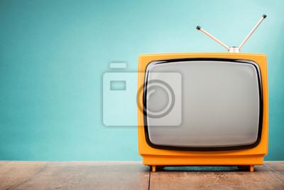Bild Retro alten orange TV-Receiver auf Tisch Front Steigung Aquamarin Wand Hintergrund. Vintage Art gefiltertes Foto