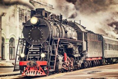 Bild Retro Dampfzug fährt vom Bahnhof ab.