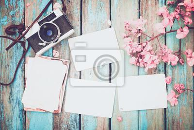 Bild Retro-Kamera und leere alte Instant Papier Fotoalbum auf Holztisch mit Blumen Grenze Design - Konzept der Erinnerung und Nostalgie im Frühjahr. Vintage-Stil
