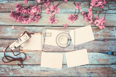 Bild Retro-Kamera und leere alte Instant-Papier Fotoalbum auf Holztisch mit Blumen Grenze Design - Konzept der Erinnerung und Nostalgie im Frühjahr. Vintage-Stil