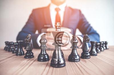 Bild Retrostilbild eines Geschäftsmannes mit den umklammerten Händen, die Strategie mit Schach planen, stellt auf einem alten Holztisch dar.