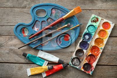 Bild Rohre mit Farben, Bürsten und Aquarellen auf Holztisch