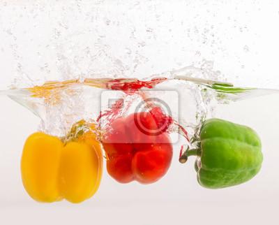 Roten gelben grünen Paprika in Spritzwasser auf weißem backgroun