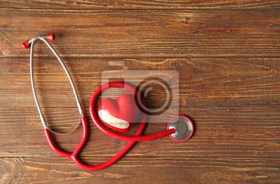 Bild Rotes Herz und Stethoskop auf hölzernem Hintergrund. Gesundheits-Konzept