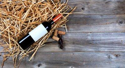 Bild Rotweinflasche mit Weinweinkorkenzieher auf Stroh
