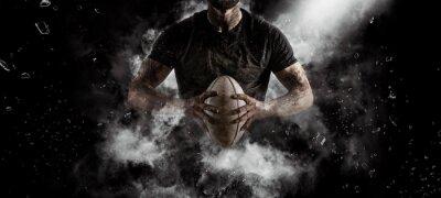 Bild Rugby player in action on dark