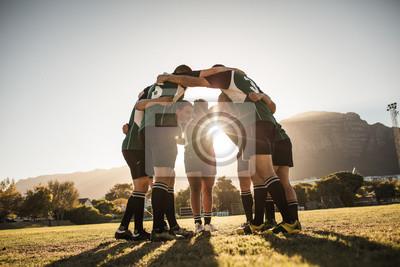 Bild Rugby players huddling on sports field