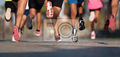 Bild Running children, young athletes run in a kids run race,running on city road detail on legs,running in the light of morning