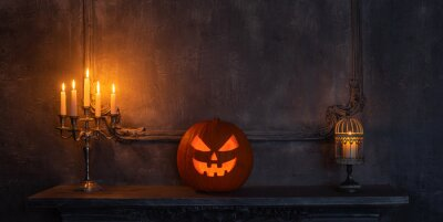Bild Scary laughing pumpkin and old skull on ancient gothic fireplace. Halloween, witchcraft and magic.