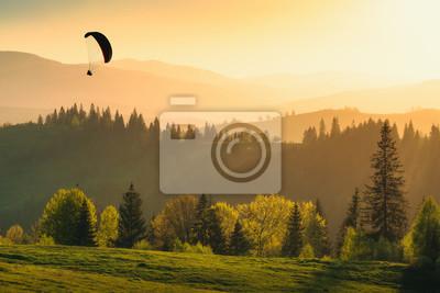 Schattenbild des Gleitschirms über dem Gebirgstal bei Sonnenuntergang