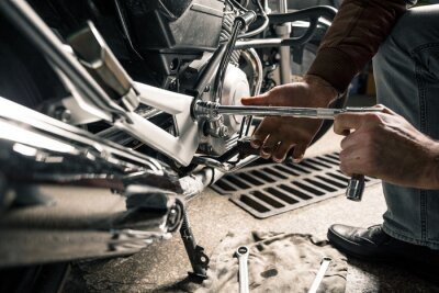 Bild Schließen Sie oben von den Händen des Mannes mit Motorrad in der Garage