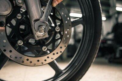 Bild Schließen Sie oben von der Hand des Mannes, die Befestigungsschlüssel nahe dem Fahrzeug des Motorrads hält.