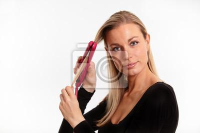 Schöne blonde Frau Begradigung ihre Haare