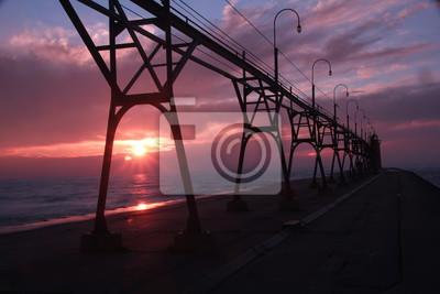 Schöne Brücke und Leuchtturm über den Sonnenuntergang.