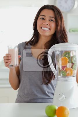 Schöne Frau mit einem Mixer, während Sie einen Drink