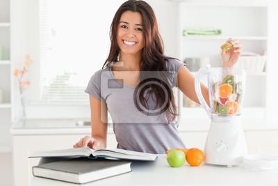 Schöne Frau Rücksprache mit einem Notebook beim Ausfüllen einen Mixer wi