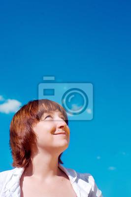 Schöne junge Frau auf der Suche nach oben in den blauen Himmel