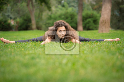 Schöne junge Frau macht Dehnübungen im Park.