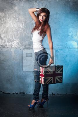 Schöne junge Frau mit Koffer mit britischer Flagge