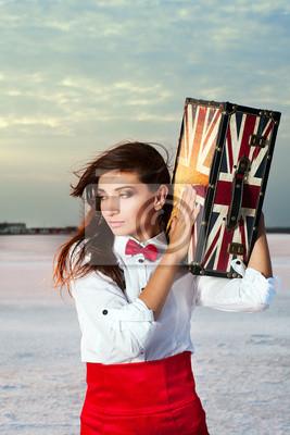 Schöne junge Frau mit Koffer mit britischer Flagge im Freien