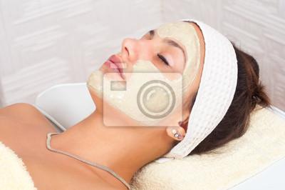 Schöne junge Frau mit natürlichen Gesichtsmaske