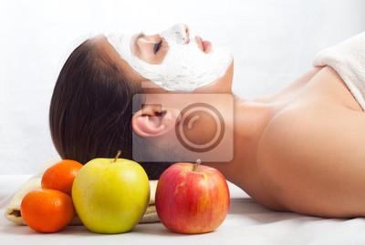 Schöne junge Frau mit natürlichen Gesichtsmaske auf ihrem Gesicht