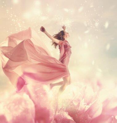 Schöne junge Frau springt auf einem riesigen Blumen