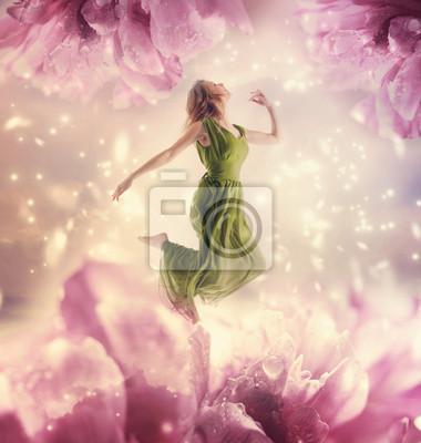 Schöne junge Frau springt auf riesigen Blumen