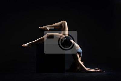 Schöne junge passende Frau mit dem dünnen muskulösen Körper in der Sportkleidung, die Sportübung tut. Ganzansicht, Seitenansicht, Studioaufnahme, schwarzer Hintergrund.