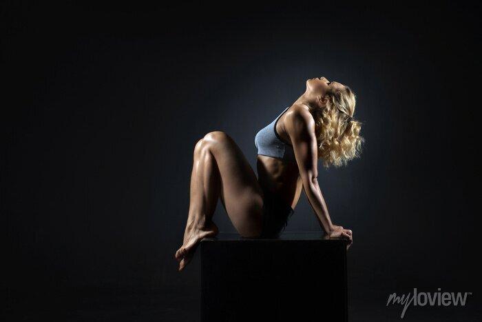 Bild Schöne junge passende Frau mit dem dünnen muskulösen Körper in der Sportkleidung, die Sportübung tut. Ganzansicht, Seitenansicht, Studioaufnahme, schwarzer Hintergrund.
