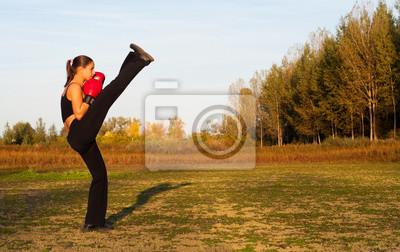 Schöne Kickboxen Mädchen Ausübung High Kick in der Natur