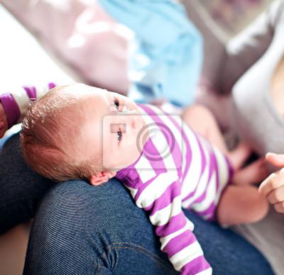 Schöne kleine Baby auf dem Schoß Mütter