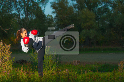 Schöne Mädchen, die Ausübung Kickboxen Kick in der Natur
