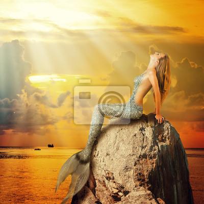 schöne Meerjungfrau sitzt auf einem Felsen