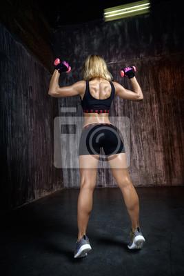 Schöne muskulöse Frau tut Übung mit Hanteln auf einem grauen Hintergrund im Studio. Die Rückansicht der sexy junge blonde Frau Training im Fitnessstudio.