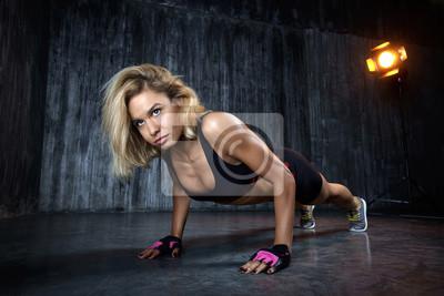 Schöne muskulöse Frau tut Übung Pushups auf einem grauen Hintergrund im Studio. Die Frontansicht der sexy junge blonde Frau Training in der Grange-Turnhalle.