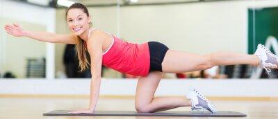Schöne sportliche Frau, die Übung an der Gymnastik