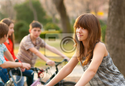 Schöne Teenager-Mädchen mit ihren Freunden auf Fahrrädern