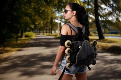 Bild Schöner Mädchen Brunette mit Rucksack hinter dem Rücken in welche Rollschuhen