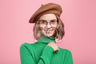 Bild Schönes französisches Mädchen schaut herrlich in Kamera, zeigt die weißen perfekten Zähne, drückt das Positive, froh aus, um ihren Erfolg mit den nahen Leuten zu teilen, lokalisiert über rosa Hintergr
