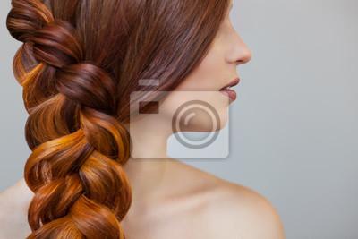 Bild Schönes Mädchen mit langen roten Haaren, geflochten mit einem französischen Geflecht, in einem Schönheitssalon. Professionelle Haarpflege und Frisuren.