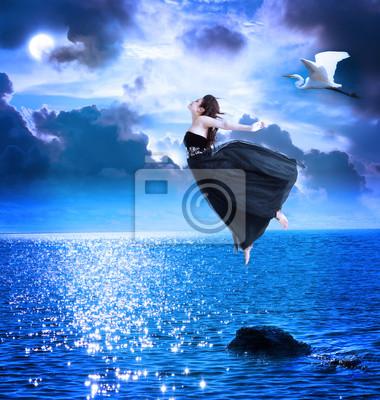 Schönes Mädchen springen in den blauen Nachthimmel