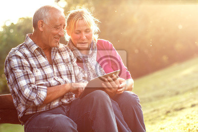 Bild Senior couple sitting on a park bench with tablet